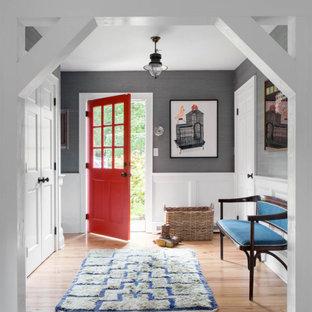 ニューヨークの片開きドアビーチスタイルのおしゃれな玄関ロビー (グレーの壁、無垢フローリング、赤いドア、茶色い床、羽目板の壁、壁紙) の写真