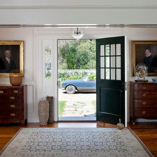 This is an example of a beach style front door in Boston with white walls, a single front door and a green front door.