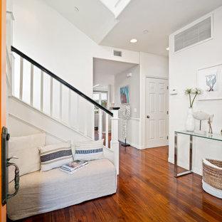Single front door - coastal dark wood floor and brown floor single front door idea in Los Angeles with white walls and an orange front door