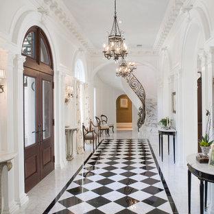 Inspiration pour un grand hall d'entrée traditionnel avec un mur blanc, une porte double, une porte en bois foncé, un sol en marbre et un sol multicolore.