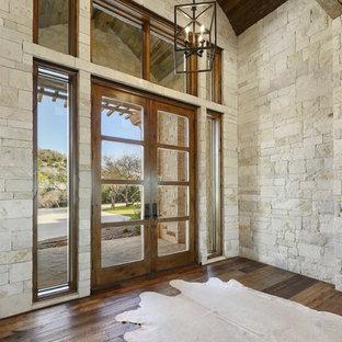 Entryway - huge cottage dark wood floor and black floor entryway idea in Austin with yellow walls and a brown front door