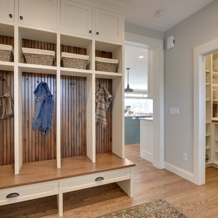 Farmhouse medium tone wood floor mudroom photo in Minneapolis with gray walls
