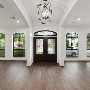 Foto de puerta principal tradicional renovada, grande, con paredes blancas, suelo laminado, puerta doble, puerta de madera oscura y suelo marrón