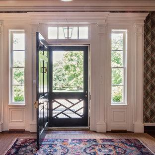 Foto på en stor vintage foajé, med flerfärgade väggar, mellanmörkt trägolv, en enkeldörr och en grön dörr