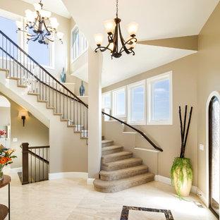 Пример оригинального дизайна: огромное фойе в классическом стиле с бежевыми стенами, мраморным полом, одностворчатой входной дверью и входной дверью из дерева среднего тона