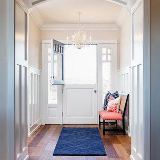 Idéer för en maritim foajé, med beige väggar, mellanmörkt trägolv, en tvådelad stalldörr och en vit dörr