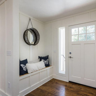 Inredning av en maritim mellanstor ingång och ytterdörr, med vita väggar, mellanmörkt trägolv, en enkeldörr, en vit dörr och brunt golv