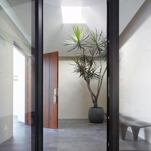 На фото: вестибюль среднего размера в современном стиле с белыми стенами, бетонным полом, одностворчатой входной дверью, входной дверью из дерева среднего тона и серым полом с