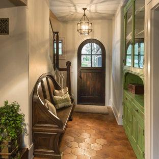ミルウォーキーの片開きドアエクレクティックスタイルのおしゃれな玄関ロビー (白い壁、テラコッタタイルの床、濃色木目調のドア) の写真