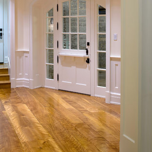 Large elegant medium tone wood floor entryway photo in Los Angeles with white walls and a white front door