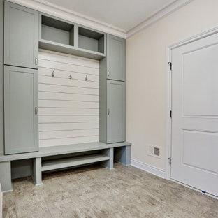 デトロイトの広い片開きドアトラディショナルスタイルのおしゃれなマッドルーム (ベージュの壁、ラミネートの床、白いドア、グレーの床) の写真