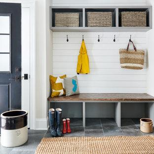 Ispirazione per un ingresso con anticamera tradizionale con pareti bianche, una porta singola, una porta nera e pavimento grigio