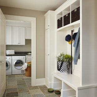 Cette photo montre une entrée chic de taille moyenne avec un mur beige, un sol en ardoise, un vestiaire et un sol beige.