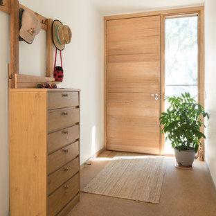 Inredning av en retro mellanstor ingång och ytterdörr, med vita väggar, korkgolv, en enkeldörr, ljus trädörr och beiget golv