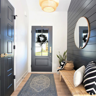 Mid-sized danish light wood floor and beige floor entryway photo in Grand Rapids with a black front door and black walls