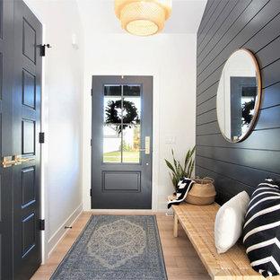 Bild på en mellanstor skandinavisk hall, med ljust trägolv, en enkeldörr, en svart dörr, svarta väggar och beiget golv