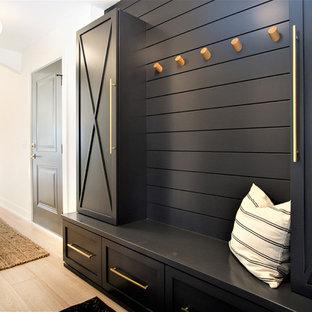 グランドラピッズの中くらいの片開きドア北欧スタイルのおしゃれなマッドルーム (白い壁、淡色無垢フローリング、ベージュの床、黒いドア) の写真