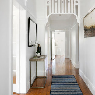 Photo of a transitional entry hall in Sydney with white walls, medium hardwood floors, a single front door, a glass front door and brown floor.