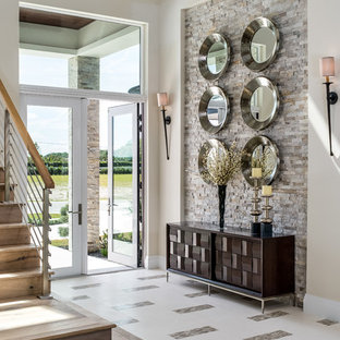 Example of a large transitional white floor and porcelain floor entryway design in Miami with beige walls and a glass front door