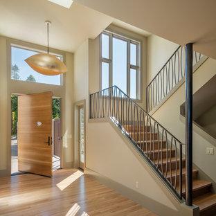 Großer Moderner Eingang mit Foyer, beiger Wandfarbe, hellem Holzboden, Drehtür, heller Holztür und beigem Boden in Seattle
