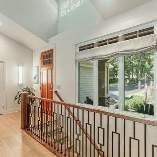 グランドラピッズの中くらいの片開きドアコンテンポラリースタイルのおしゃれな玄関ロビー (白い壁、淡色無垢フローリング、オレンジのドア、黄色い床) の写真