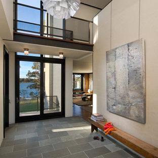 Exemple d'une entrée moderne avec un mur beige, une porte en verre, un sol en ardoise et un sol gris.