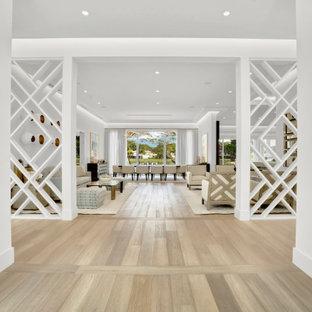 マイアミの広い両開きドアコンテンポラリースタイルのおしゃれな玄関ロビー (白い壁、淡色無垢フローリング、濃色木目調のドア、ベージュの床、格子天井) の写真