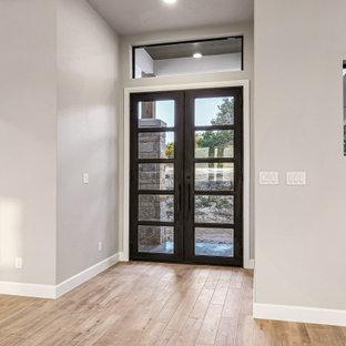 Пример оригинального дизайна: фойе среднего размера в стиле кантри с бежевыми стенами, полом из керамогранита, двустворчатой входной дверью, черной входной дверью, бежевым полом и сводчатым потолком