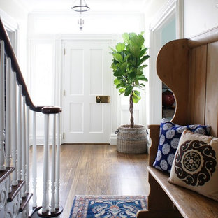 Example of a mid-sized classic medium tone wood floor single front door design in New York with white walls and a white front door