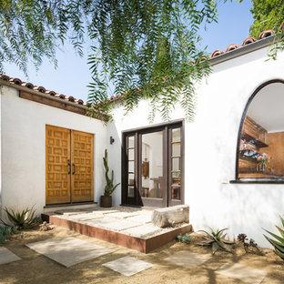 Imagen de puerta principal mediterránea, pequeña, con puerta doble, puerta de madera en tonos medios, paredes blancas, suelo de cemento y suelo gris