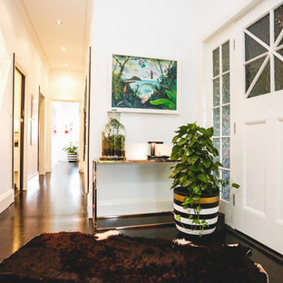 Small island style dark wood floor and black floor entryway photo in Sydney with white walls and a white front door