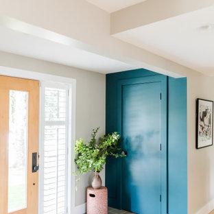 На фото: большое фойе в стиле фьюжн с разноцветными стенами, светлым паркетным полом, одностворчатой входной дверью, входной дверью из светлого дерева, бежевым полом и многоуровневым потолком с