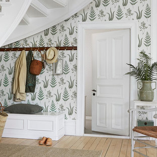 Design ideas for a mid-sized country mudroom in Boston with green walls, light hardwood floors, a single front door and a white front door.