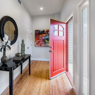 Inspiration for a contemporary bamboo floor entryway remodel in Los Angeles with white walls and a red front door