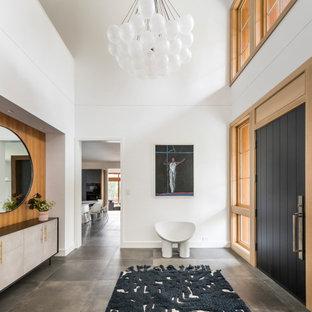 ボストンの片開きドアコンテンポラリースタイルのおしゃれな玄関ドア (黒いドア、白い壁、グレーの床、板張り壁、三角天井) の写真