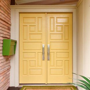 Photo of a large midcentury front door in Houston with beige walls, slate floors, a double front door, a yellow front door and grey floor.