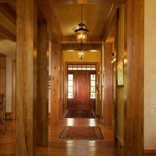 Ispirazione per una porta d'ingresso con pareti beige, pavimento in legno massello medio, una porta singola e una porta in legno bruno