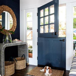 Cette photo montre une porte d'entrée bord de mer de taille moyenne avec un mur blanc, un sol en bois foncé, une porte double et une porte bleue.
