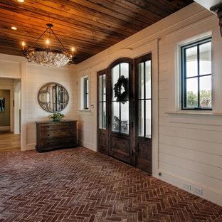 Foto di un ingresso con vestibolo classico con pareti bianche, pavimento in mattoni, una porta singola e una porta in legno scuro
