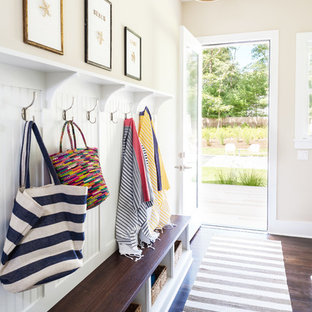 Inspiration for a mid-sized coastal dark wood floor entryway remodel in New York with beige walls and a glass front door