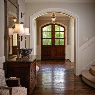 Imagen de distribuidor clásico, de tamaño medio, con puerta de madera oscura, paredes grises, suelo marrón, suelo de madera oscura y puerta doble