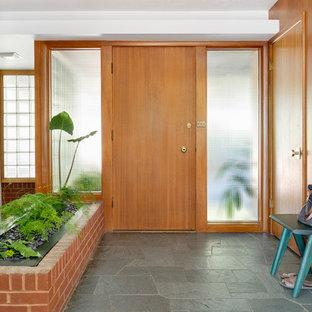 Diseño de distribuidor retro, de tamaño medio, con paredes blancas, suelo de pizarra, puerta simple, puerta de madera en tonos medios y suelo verde