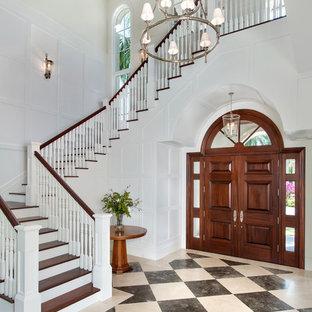 マイアミの大きい両開きドアトロピカルスタイルのおしゃれな玄関ロビー (白い壁、大理石の床、濃色木目調のドア、マルチカラーの床) の写真