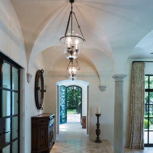 Entryway - huge mediterranean limestone floor and beige floor entryway idea in Houston with white walls and a metal front door