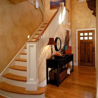Immagine di un ingresso o corridoio chic con pareti arancioni, una porta singola e una porta in legno bruno