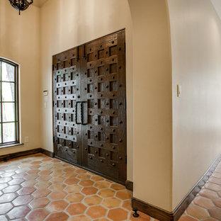 Esempio di una grande porta d'ingresso mediterranea con pareti beige, pavimento in terracotta, una porta a due ante e una porta in legno scuro