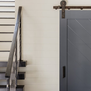 Example of a mid-sized trendy slate floor entryway design in Boston with white walls and a glass front door