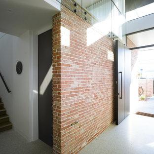 Foto på en mellanstor industriell foajé, med vita väggar, granitgolv, en pivotdörr, metalldörr och svart golv