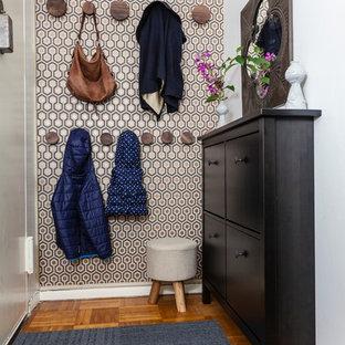 Cette photo montre un petit hall d'entrée chic avec un sol en bois brun, une porte simple, une porte blanche et mur métallisé.