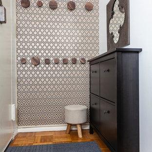 Immagine di un piccolo ingresso tradizionale con pavimento in legno massello medio, una porta singola, una porta bianca e pareti con effetto metallico